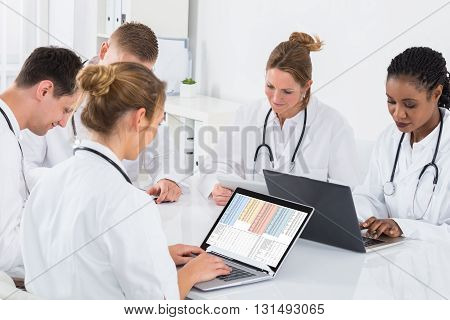 Group Of Multi-racial Doctors Using Laptop At Desk