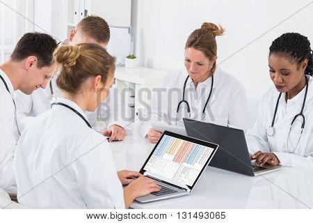 Group Of Multi-racial Doctors Using Laptop At Desk