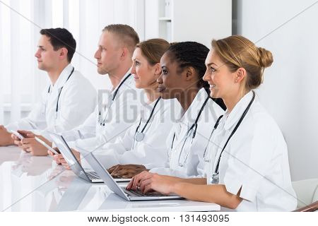Group Of Multi-racial Doctors Using Laptop In Meeting