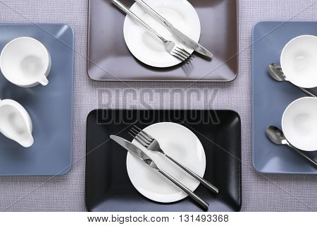 Empty dishes with silver flatware on grey background