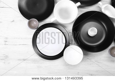 Black and white empty dishes on white wooden background.