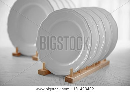 Set of new white plates on wooden table, indoors