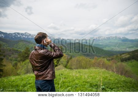 Man calling phone on the mountain. Outdoors shot in the mountains