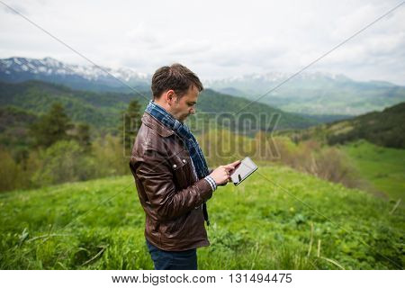 young man touching the tablet pc on the top of mountain.
