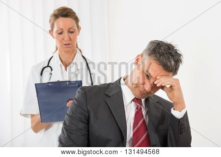 Doctor With Clipboard Standing Behind The Businessman Having Headache In Clinic