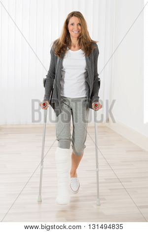 Happy Mature Woman With Fractured Leg Holding Crutches While Walking