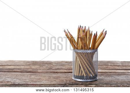 Pencils in metal holder on white background