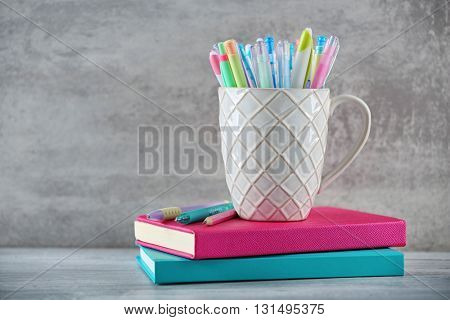 Pens in ceramic cup on grey background