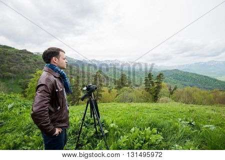 Professional photographer takes photos with camera on peak of rock.