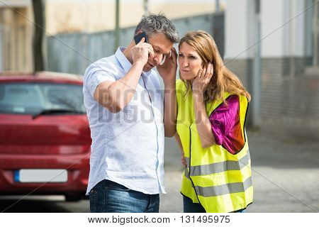 Couple Calling For Service On Mobile Phone With Broken Down Car At Street