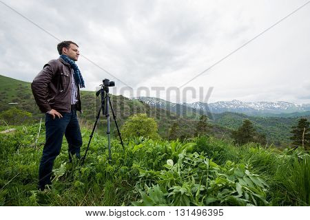 hiker taking photo of beautiful mountain landscape with camera.