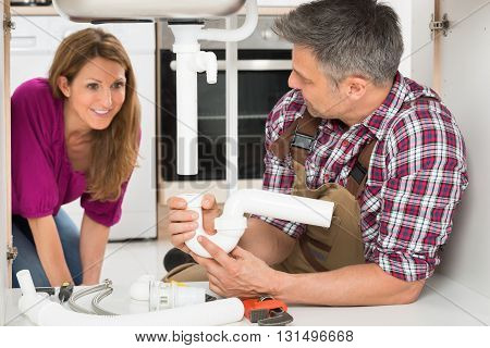 Smiling Woman Pointing At Sink Pipe Hold By Male Plumber