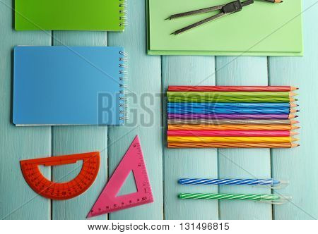 School set with notebooks, divider and colored pencils on wooden blue background