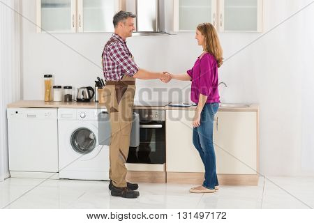Male Repairman Shaking Hands With Smiling Woman In Kitchen