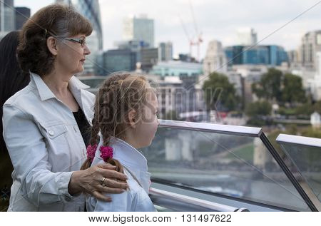 Elderly woman and granddaughter enjoying the London view. Background includes modern building City of London, business and banking aria