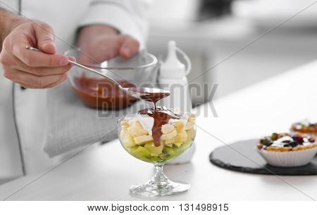 Male hand pouring chocolate  sauce on fruit dessert.