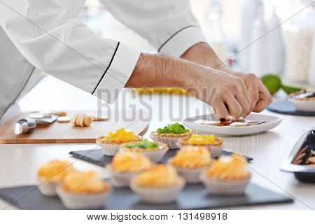 Male chef decorating cookies with sliced banana.