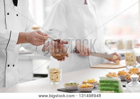Male chef  pouring chocolate  sauce on a fruit dessert.