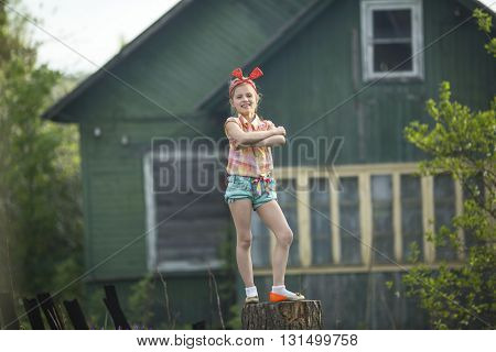 Funny little girl standing on a stump near the country house.