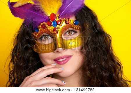 woman face closeup in carnival masquerade mask with feather, beautiful girl portrait on yellow color background, long curly hair