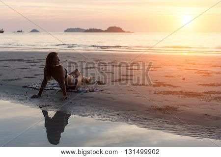 Young beautiful woman lying on the beach during sunset.
