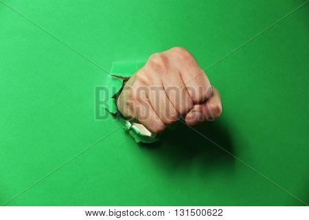 Male fist punching through green paper