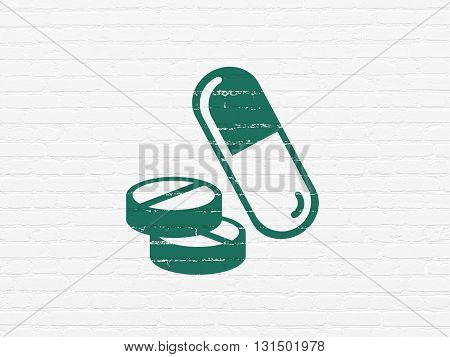 Health concept: Painted green Pills icon on White Brick wall background