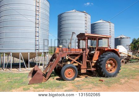 Antique rusted tractor with bulk storage silos on farmland under a blue sky in Western Australia.