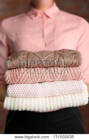 Stack of knitted clothes in female hands closeup