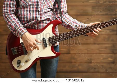 Young man playing electric guitar on wooden background