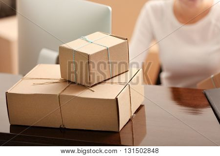 Delivery concept. Woman signs papers among parcels, close up
