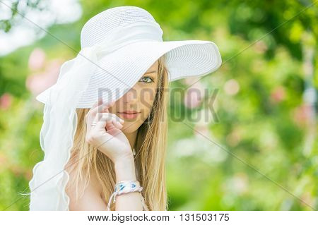 Portrait of beautiful natural young woman with white hat in the rose garden