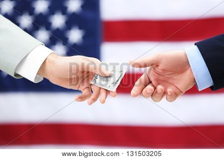 One groom giving a condom to another man on American flag background
