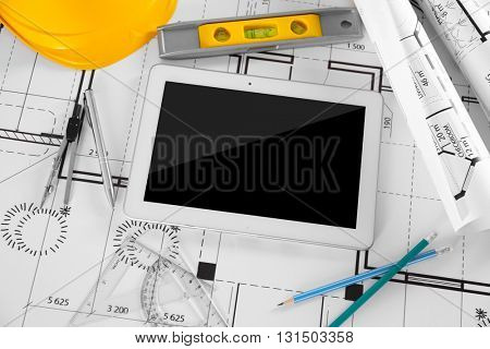 Construction blueprints with tools and tablet