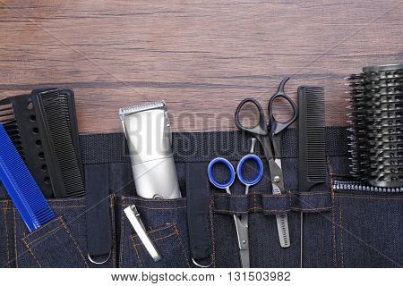 Professional hairdressing equipment in black case on wooden table background
