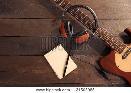 Guitar with headphones and notebook on wooden background