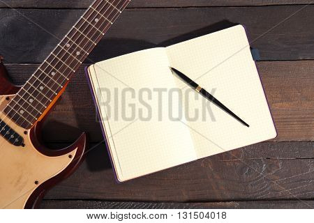Guitar and notebook on wooden background