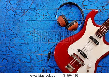 Electric guitar with headphones on blue wooden background