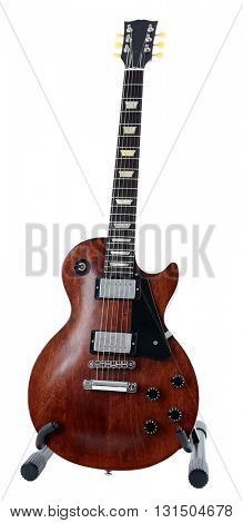Brown electric guitar on a stand, isolated on white