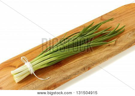 Fresh green onion on wooden board. Isolated on white background.