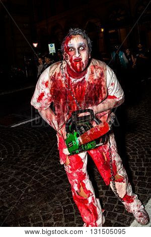 Bologna, Italy - May 21, 2016: Bologna zombie apocalypse walk. Halloween costume maniac with bloody clothes and chainsaw and scares people.