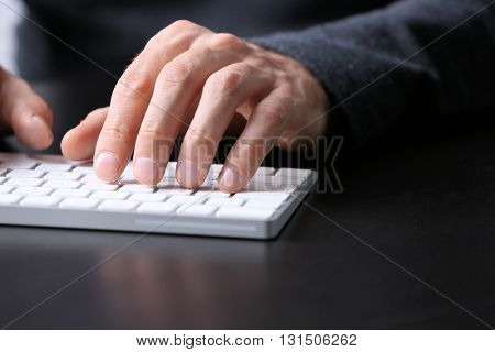 Male hands typing on wireless keyboard at table closeup