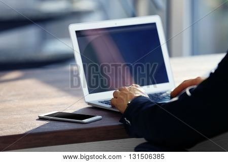 Man's hands using laptop at the table in office against the window