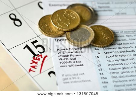 A red tax mark in the calendar, euro coins and tax form, close up