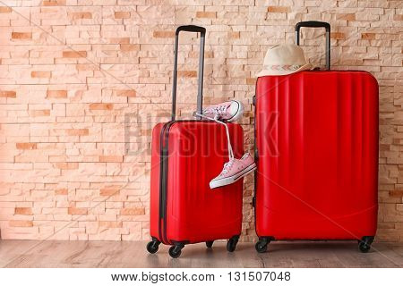 Red suitcases with hat and gumshoes on brick wall background