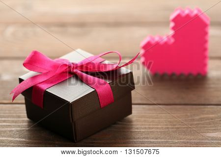 Gift box and decorative hearts on wooden background