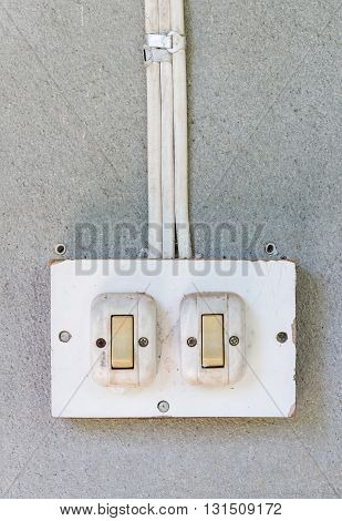 Old double switch on the cemetn wall of the rural house.