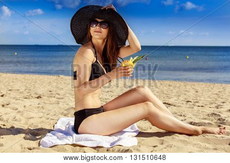 Beautiful Sexy Girl In Swimwear Sitting On Sandy Beach. Sea Coast Visible In The Background.