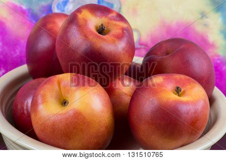 Nectarines Isolated in a yellow bowl with a colorful background.