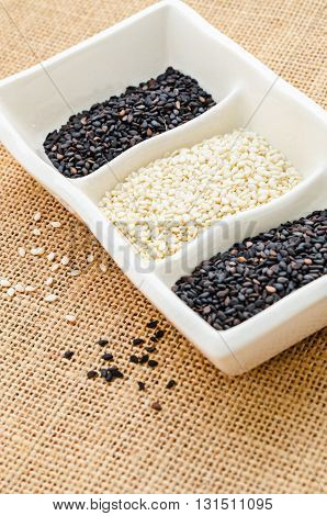 white sesame and black sesame in white cup on sack background.